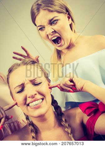 Two young pretty women being mad at each other having argue fight pulling hair. Friendship rivaly and envy problems.