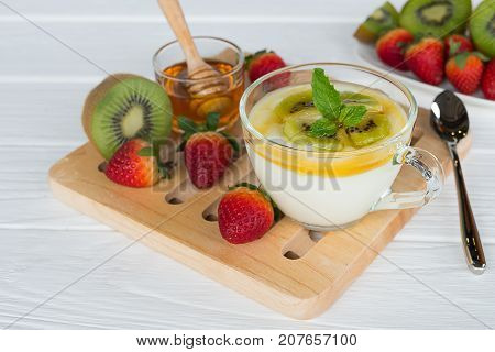Kiwi yogurt, strawberry with kiwi fruit and strawberry for breakfast in the morning on a white wood background.