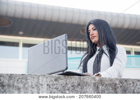 Busy female freelancer using laptop outdoors. Concentrated young Hispanic businesswoman analyzing report while working out of office. Technology concept