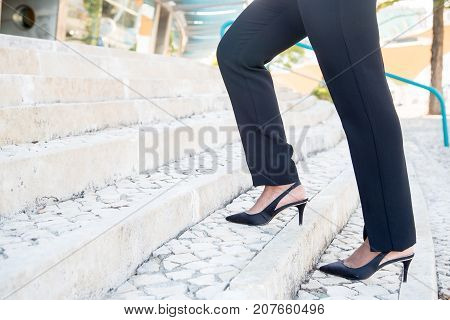 Close-up of unrecognizable businesswoman in fashionable black trousers moving up stairs. Stylish woman making step outdoors. Ladder of success concept