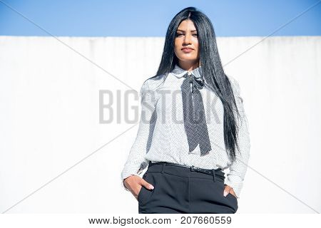 Confident beautiful businesswoman posing for camera and holding hands in trousers pockets outdoors. Serious fashionable business lady standing and looking at camera. Leadership concept