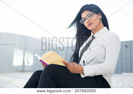 Confident female entrepreneur reading business book to achieve success. Serious intelligent Hispanic lady resting with book outdoors. Self-education concept