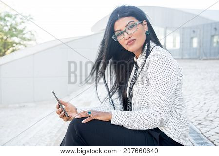 Confident smart woman using modern device outdoors and looking at camera. Serious attractive Hispanic business lady checking email via smartphone. Business outdoors concept