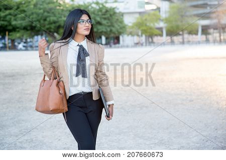 Dreamful young business lady walking over city and enjoying modern lifestyle. Confident attractive Hispanic student coming home after classes. Successful lady concept
