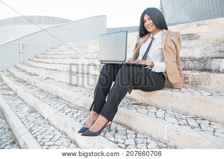 Happy Hispanic female manager enjoying freelance work and using laptop outdoors. Cheerful successful entrepreneur working out of office and sitting on stairs. Technology concept