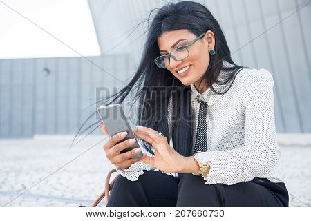 Happy Hispanic woman surfing net on smartphone or reading message. Cheerful young businesswoman using mobile phone outdoors. Gadget addiction concept