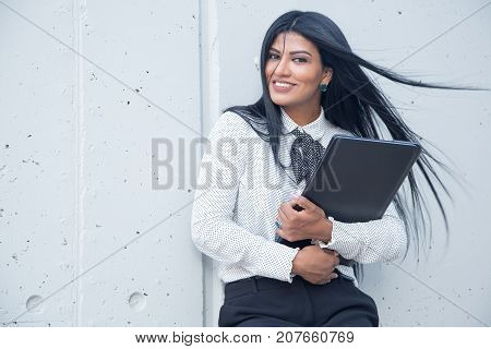 Happy young female entrepreneur embracing laptop and looking at camera. Cheerful successful Hispanic businesswoman leaning on wall. Modern lifestyle concept