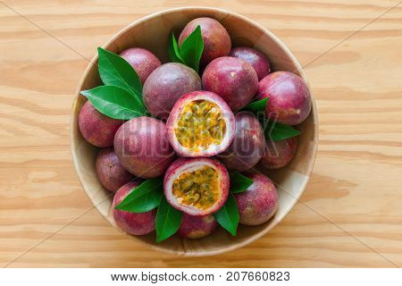 Fresh passion fruit in wood bowl on wood table in top view flat lay with copy space for background or wallpaper. Ripe passion fruit so delicious sweet and sour. Passion fruit is tropical fruit.