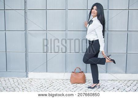 Playful businesswoman enjoying stroll after work and adjusting shoe while leaning on wall. Cheerful beautiful white collar worker looking at camera while walking over street. Fashion concept
