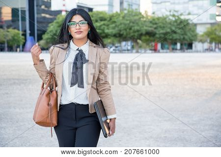 Serious successful business lady carrying bag and laptop and looking at camera while coming home after work. Confident Hispanic lawyer always taking laptop to meeting. Modern lady concept