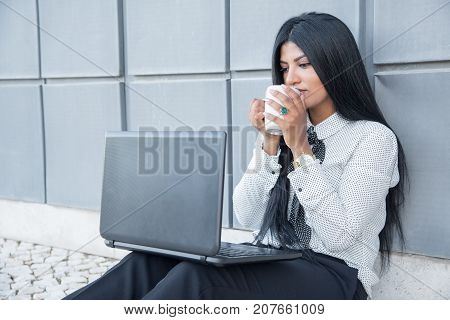 Serious businesswoman examining report outdoors while drinking coffee from mug. Or concentrated female manager reading article on Internet. Technology concept