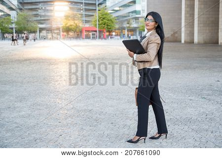 Stylish female lawyer walking over city and looking at camera. Confident intelligent businesswoman hurrying off to meeting with client. Manager concept