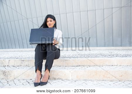 Successful female entrepreneur working on laptop and sitting on stairs outdoors. Modern Hispanic businesswoman opening portable computer to start working. Busy life concept