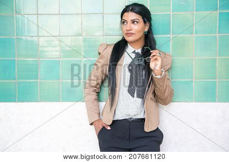 Thoughtful smart businesswoman holding eyeglasses and looking away. Serious confident young Hispanic lady in jacket standing against tile wall and reflecting about business. Ambition concept