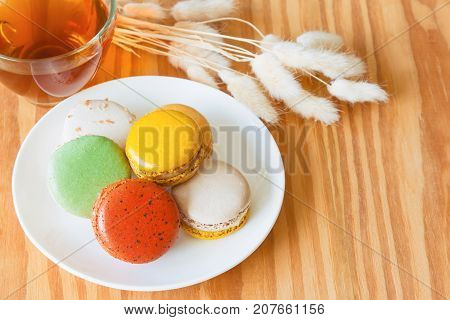 Colorful French macaron or Italian macaron on white plate. Homemade delicious macaron and tea on wood table with copy space for background or wallpaper. Macaron is popular dessert for served with tea. Macaron and tea ready to served.