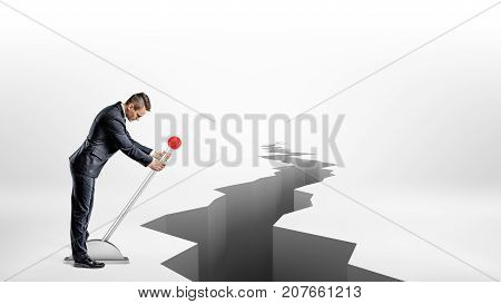 A businessman turns a large metal lever while standing beside a long earthquake rift on white background. Change circumstances. Use all you can get. Hostile business environment. poster