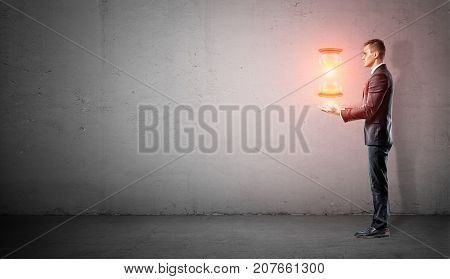 A businessman stands in side view on concrete background with his harms under a hovering glowing hourglass. Master of time. Keep time in check. Time control.