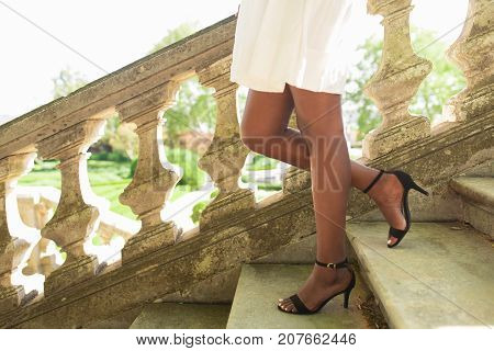Cropped view of legs of black woman wearing high heeled shoes and walking down stairs in park with railing in background. Side view.