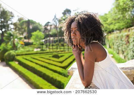 Closeup portrait of pensive young attractive African American woman standing and leaning on stone railing in park with beautiful garden in background. Side view.