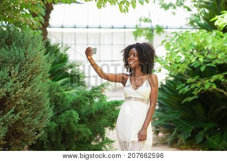 Closeup portrait of smiling young attractive African American woman holding smartphone, taking selfie photo and standing in park with plants in background