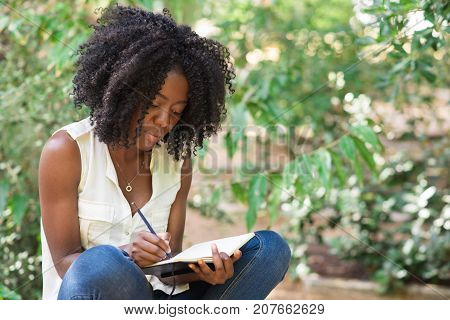 Closeup portrait of young attractive black woman working, making notes and sitting in park