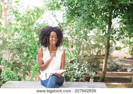 Closeup portrait of smiling young attractive black woman working, making notes and sitting on bench in park
