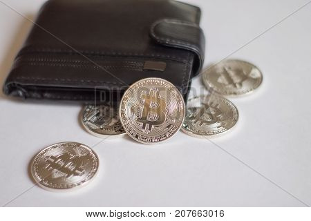 Bitcoins from the wallet. Coins are located near the wallet on a light background.