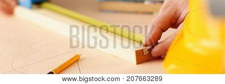 Arms of worker measuring wooden bar closeup. Manual job, DIY inspiration, improvement job, fix shop graphic, joinery startup, workplace idea, designer career, ruler, industrial education concept