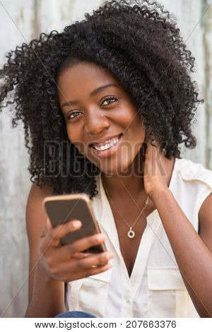 Portrait of positive young African-American woman wearing blouse using smartphone, looking at camera and smiling. Communication concept