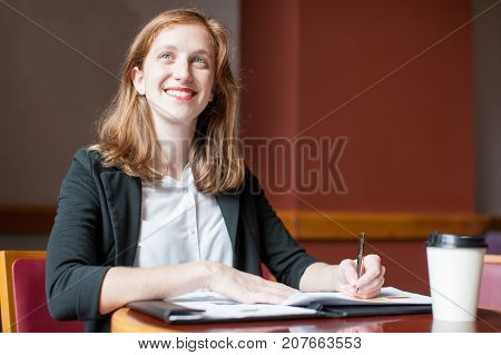 Closeup portrait of smiling attractive young woman writing, working with diagrams and sitting at table in cafe