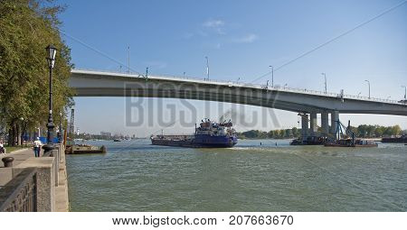 Rostov-on-DonRussia -September 162017: Passage of ships along the Don River under a new bridge.On the waterfront are pedestrians
