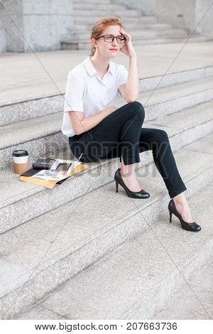 Closeup portrait of pensive attractive young business woman looking away and sitting on stairs outdoors