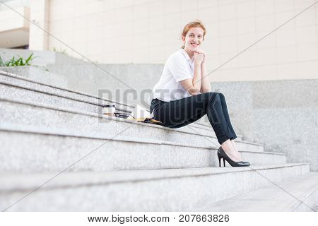 Closeup portrait of smiling attractive young business woman looking at camera and sitting on stairs outdoors. Low angle side view.