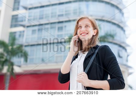 Closeup portrait of smiling young business woman calling on smartphone and standing with big city building in background