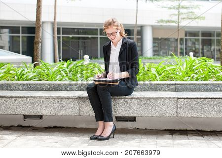 Closeup portrait of smiling young business woman making notes, working and sitting on flowerbed in city