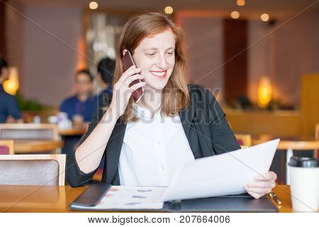 Closeup portrait of smiling attractive young woman working, holding paper, calling on phone and sitting at table in cafe with blurred interior and people in background