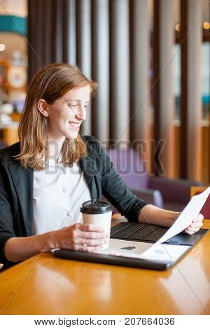 Closeup portrait of smiling attractive young woman working with diagrams, drinking coffee and sitting at table in cafe