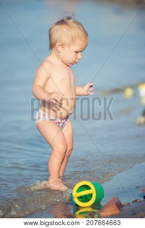 Baby playing on the sandy beach and in sea water. Cute little kid with toys on sand tropical beach. Ocean coast.