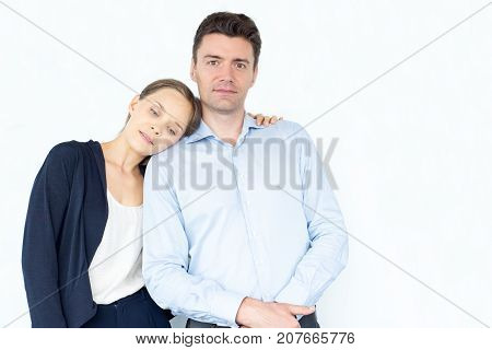 Confident businessman embraced by loving wife looking at camera. Serious young couple having relationship difficulties. Loving wife supporting husbands. Relationship concept