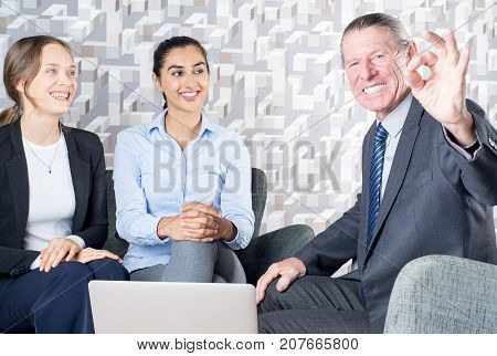 Excited senior consultant solving any problems. Cheerful successful financial advisor helping lesbian couple and showing ok sign at consultation. Realtor concept