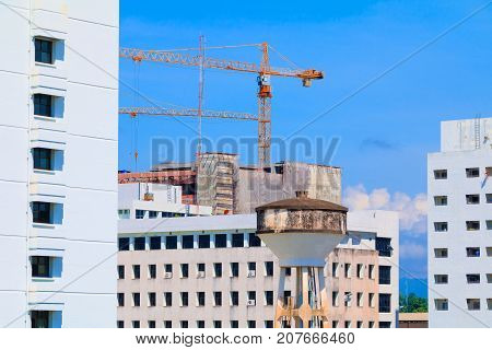 water tank and Crane Tower in construction site in develop city with copy space add text