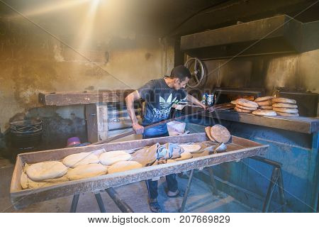 Imilchil Morocco - Jan 10 2017: Worker in traditional bread bakery. Morocco