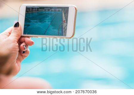 woman hand holding her phone recording swimming pool activities selective focus and room for text or copy space
