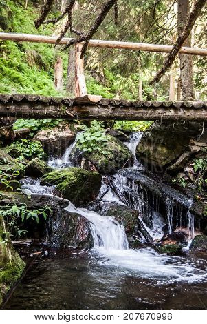 waterfall with wooden bridge above on Bila Opava river in Jeseniky mountains near Praded hill in Czech republic