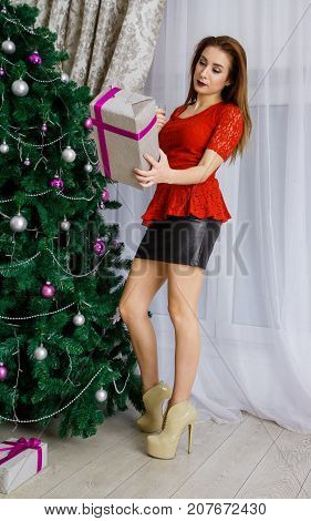 Girl with a glass of champagne and a gift at a Christmas tree