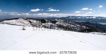 winter Beskids mountains panorama with Babia Gora Pilsko and other hills on polish-slovakian borderland from Magurka Wislanska hill in Silesian Beskids mountains near Wisla resort in Poland