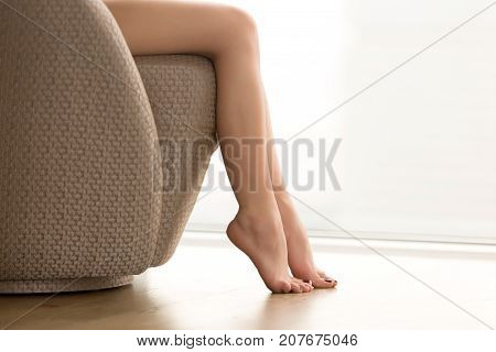 Close up view of beautiful bare female legs, young woman sitting barefoot on cozy chair relaxing at home, enjoying soft waxed skin, foot rest, no shoes, epilation and depilation, copy space