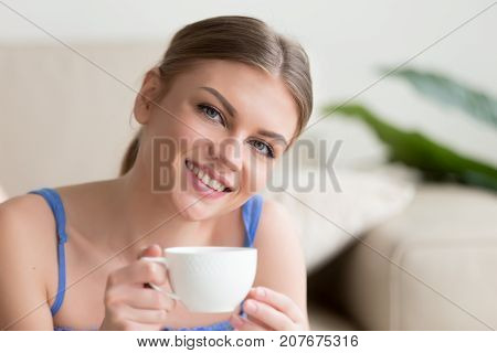 Young smiling attractive woman enjoying instant brewed coffee in the morning, happy lady holding cup of tea and looking at camera, pleasant day at home with hot drink in mug, head shot portrait