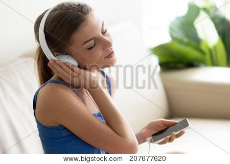 Relaxed calm young woman enjoys music, teenager wearing headphones listens to high quality sound using player application on smartphone, teen girl meditating at home with ambient chill audio playlist
