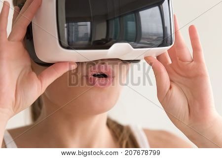 Young surprised woman first time trying VR headset, amazed girl watching 3d film tour in virtual reality glasses, cant believe her eyes, experiencing fantastic presence effect in ar world, close up